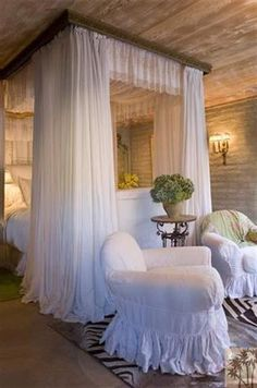 a fanciful master suite with a private flagstone patio, a reception area, a dressing room and a separate sleeping chamber. Sandblasted wood walls balance a feminine canopy bed with flowing white curtains, while wall sconces cast a soft glow across the room.