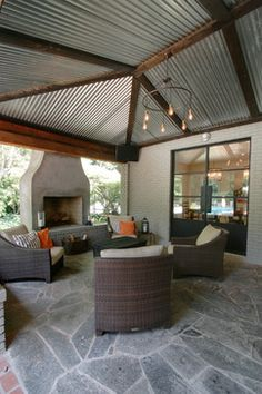 Outdoor living room, contemporary patio. Rustic accents with corrugated metal. Love the vintage lighting.