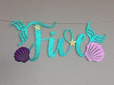 Five Banner Mermaid Theme with mermaid fins, sea shell and starfish. The word Five is roughly 10.75 wide X 4 tall. With the sea shells on either end the overall banner is roughly 24 wide. It is attached to a 6 long gold and white twine string. There is a light purple shell on the e. You