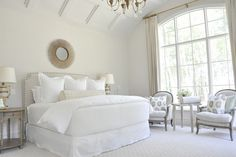 Urban Grace Interiors  Gorgeous monochromatic modern French bedroom design with off-white walls paint color, soft gray linen headboard with nailhead trim,white & gray chairs, sunburst mirror and urn lamps.