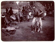 Photograph (black and white) from an album; Masked performer facing drummers. Ikot Ekpene, Nigeria, 22 November 1905. Gelatin silver print