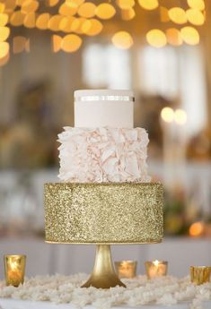 three tiered wedding cake with blush floral and gold glitter layers
