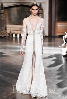 Could be modest long sleeve a-line gown with deep v-neck and high slit. See photos of Inbal Dror's Fall 2015 wedding dress collection.