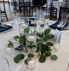 Three cylinder vases with floating candles and greenery.