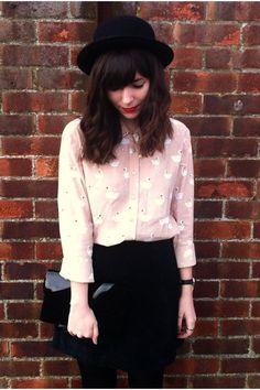 pastel flamingo print blouse, black mini skirt, tights and bowler hat.