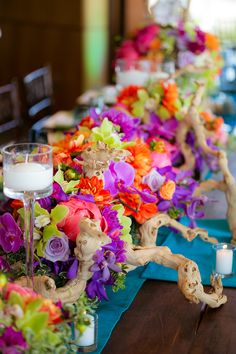 This imaginative beach wedding is exquisitely styled with sunset hued blossoms, natural driftwood, and orchid-enhanced Manzanita branches enlivening the modern architecture of this popular venue. Peony, dahlia, and rose filled centerpieces are accented with vivid chartreuse orchids and various blue-green succulents. Photos:The Youngrens. Wedding Coordinator: Crown Weddings. Florals: Adorations Botanical Artistry.