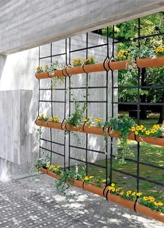 A true hanging garden! Think how easy this would be to hang from a pergola, thick branch, eave, tree house or kid's fort for privacy and color. Plant with annual climbers like sweet peas, morning glory or beans. It would be easy to take down at the end of the season and wouldn't take up much storage space. Seems like rope or chains could be used instead of nylon straps. Recycled rain gutters or planters could be made out of scrap wood. (Original designer and photographer unknown. Sorry.)