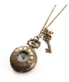 This antique bronze pocket watch necklace has a lovely vintage style key and dangling pearl charm.