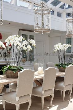 Baskets of tall white orchids are arranged on the long refectory table under the central skylight in the dining room