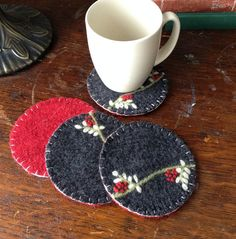 This listing is a set of four reversible coasters made from recycled wool felt. One side is a dark gray with a lovely leaves and berries embroidery