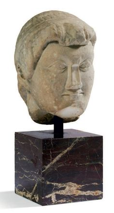 TÊTE MASCULINE ARCHAÏSANTE. Elle représente un homme, la coiffure archaïsante formée de longues mèches ondulées parallèles ceintes d'un bandeau. Marbre. Art Romain, ca. IVe siècle.