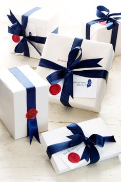 white paper, navy satin ribbon & wax stamp.