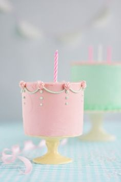 Mini pink birthday cakes, with a dark pink breast cancer ribbon on top with candle
