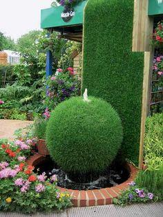 fontaine de jardin design boule en herbe dans un bassin entoure en briques