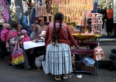 Aymara women are seen next to a stand with offering products at the witch doctor's street in La Paz, Bolivia July 31, 2015. (Photo by David Mercado/Reuters)