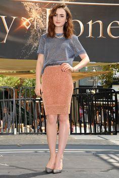 Lily Collins con falda lápiz de Bec & Bridge's, un jersey con starss, los pumps Pigalle de Louboutin y un collar cadena de Pomellato.