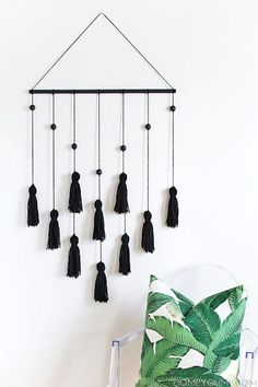 黒のタッセルを棒に結んで垂らして、モダンなインテリアアイテムとして。白い壁にも映え、お部屋のアクセントになります。