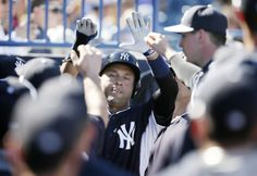 New York Yankees shortstop Derek Jeter celebrates with teammates after scoring a run during the fifth inning of an exhibition baseball game against the Philadelphia Phillies Saturday, March 1, 2014, in Tampa, Fla. (AP Photo/Charlie Neibergall)