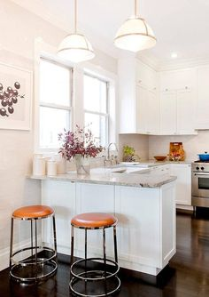 On ebony wood floors, backless chrome and orange leather barstools sit in front of a white kitchen peninsula topped with a gray granite countertop fixed against light gray glazed subway backsplash tiles and lit by white glass pendants.