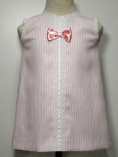 Vestido para bebe niña en pique de rayas rosas, con centro de encaje de bolillos adornado con tirabordada blanca en cuello y manga. Lazo a juego.
