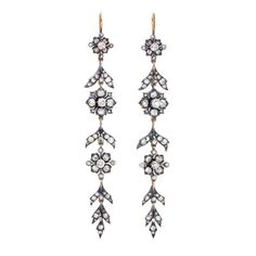 """A pair of mid Victorian articulated floral long """"shoulder duster"""" earrings, made of oxidized silver on top of 18K gold, and set with gorgeous Old Mine-cut and rose-cut diamonds. Circa 1865."""