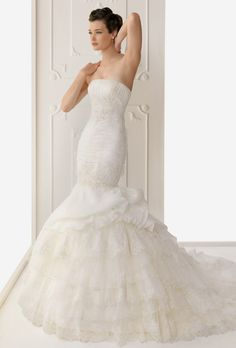 Brides: Alma Novia. Organza and lace gown with bead-work and ruffles on the asymmetrical skirt, in natural.