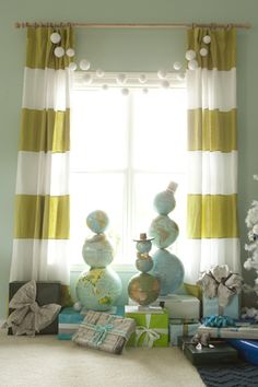 vintage globes, striped draperies, cool blue walls, styrofoam snowball garland.  Emily Henderson