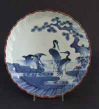 A Late 17th or Early 18th Century Japanese Blue and White Porcelain Dish Kakiemon Style, Arita Kilns c.1690-1720. Well Painted with Three Cranes (possibly red-crowned cranes) Near a Gnarled Pine Tree with Exposed Roots, there is Bamboo to the Right. The Cranes in Contrasting Positions Stand in Water that is Partly Rendered as a Brocade. R and G McPherson dealers in antique Chinese porcelain