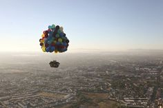 """""""Beautiful Pipedream of the Day: The """"Up"""" House in Real Life.  Here's a picture of professional cluster-balloonist Jonathan Trappe flying in a house over the city of Leon in Mexico during the last week's Leon International Balloon Festival. While this isn't the first time we've seen real life tributes to the famous floating house from Pixar's 2009 animated adventure film Up, Trappe became the first human to travel aboard such a device."""""""
