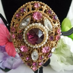 Coupon  050116 - Florenza Pink & Purple Rhinestone Brooch that is framed in Goldtone Metal. Price  This classic brooch measures just over 2 inches tall and at its widest point approximately 1.5 inches.  You can see more photos in our store at www.CCCsVintageJewelry.com $36 Have a great vintage day! Best, Coco
