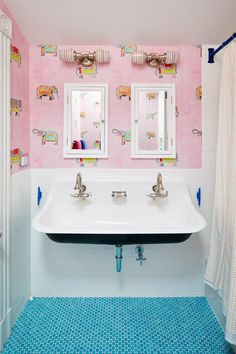The historic feel of the fixtures and tile pairs with the playfulness of the pink wallpaper in the girls' bathroom in the Arcade home.