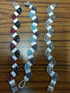 Bead weaving.  Square beads with two holes, either 3mm crystals or size 8 beads, and size 11beads between.  Increase by one crystal/8 and on 11 on each line to create a curve, and reduce by the same on each line to send the next curve in the oposite direction.