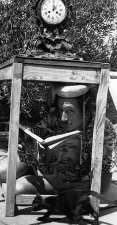 'Salvador Dali and an unidentified kitten do what passes for reading in Dalí's world.'  S)