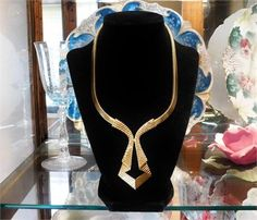 ITEM # 111503   This is a stunning statement piece created in the 1950s by Crown Trifari in an Egyptian Revival / Art Deco flare. Necklace, when open and laying flat, measures 18, the center hangs 3, and the snake chain is 1/4 wide. Necklace has a fold over clasp. Signature on center pendant, as seen in last photo, as well as signed on both ends of clasps.   Very good antique condition with typical wear due to age and handling, although it looks as though it was rarely worn, if ever...