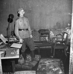 A Russian soldier stands amid rubble - next to the ripped and burnt sofa in one room of th...