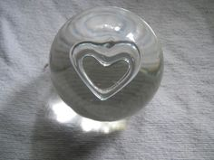 "This paperweight is clear in color, about 2 1/2"" tall and is has a heart in the center. 