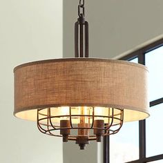 Made with metal construction and a tan burlap shade, this attractive, industrial pendant offers a blend of modernized and rustic style.