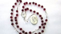This lovely chaplet is made of deep red and clear 8mm Czech glass druk beads. The center medal depicts a chalice and host on one side and St Faustina on the reverse. The large medal has the Divine Mercy image on front and the Blessed Virgin on the back. Both are made in Italy. The chaplet measures just short of 22 inches when laid flat. Instructions are included to pray this chaplet. The History of the Chaplet of The Divine Mercy In 1935, St. Faustina received a vision of an angel sent by…