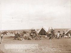 1887 - Cowboys seated around a chuckwagon at their campsite in Belle Fouche [sic] South Dakota.