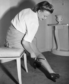 """Drawing in the seam-line on """"Makeup"""" stockings with a device made from a screw driver handle, bicycle leg clip, and an eyebrow pencil, 1942. Bettman/Corbis"""