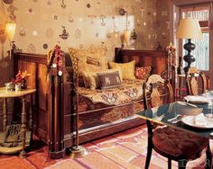 By 2006 the dining room was completely changed. There was still a daybed to recline on, but this one is 19th century French. Vintage fabrics from Turkey, Japan and China have been made into pillows and hand-embroidered Vietnamese silk lines the walls. The Fortuny sconces