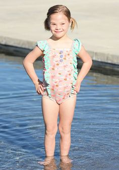 Slip and Slide Swimsuit - Matilda Jane Clothing - The Slip and Slide Swimsuit showcases pink flamingos and mint green and pink ruffles with delicate button details. It's also UV Protection 40+ to help keep your cutie safe in the sun. #matildajaneclothing #summerstyle #springstyle #kidsfashion #girlsfashion #swimsuit #swimwear