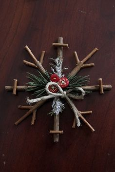 This rustic snowflake is made from twigs of wood that have been cut to proportion, then tied or wired together. The center is decorated with vintage buttons, sprigs of evergreen, tinsel and natural rope.