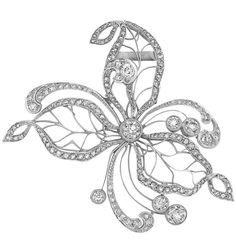 Edwardian Platinum and Diamond Flower Clip. The delicate openwork flower with…