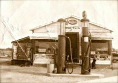 Early gas tanks at gas station.