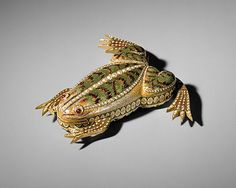 Automaton. 1820. Switzerland. Gold and green enamel automaton in the form of a frog and set with pearls. Ruby eyes. Mechanism operates the legs to cause the frog to jump and croak.