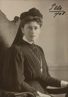 """Grã-duquesa Elizabeth Feodorovna em cerca de 1908. Ela está sentada em uma cadeira de frente voltada para a direita, mas com a cabeça voltada para a câmera. Ela está usando um vestido escuro, um lenço na cabeça e um crucifixo e em uma longa cadeia. A fotografia é assinada e datada """"Ella 1908 'no canto superior direito."""