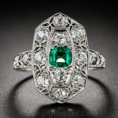 Art Deco Emerald and Diamond Ring. A petite, yet gemmy, bright green emerald is the central attraction in this exquisitely designed and executed, original early-Art Deco dinner, or right hand, ring. This extra-lovely almost antique jewel was finely hand crafted in platinum, circa 1920s, and displays an artful combination of Edwardian laciness and Art Deco geometry.