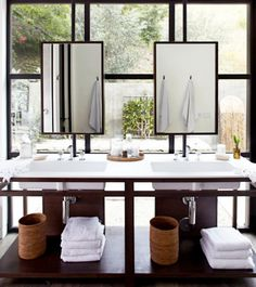 Pair of pathroom sink and mirrors in front of windows