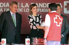 Queen Letizia shakes hands with a Spanish Red Cross worker next to the Speaker of the Lower House of the Spanish Parliament Jesus Posada (L)